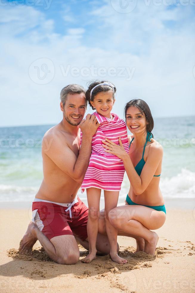 porträtt av ett ungt par i baddräkter med sin dotter foto