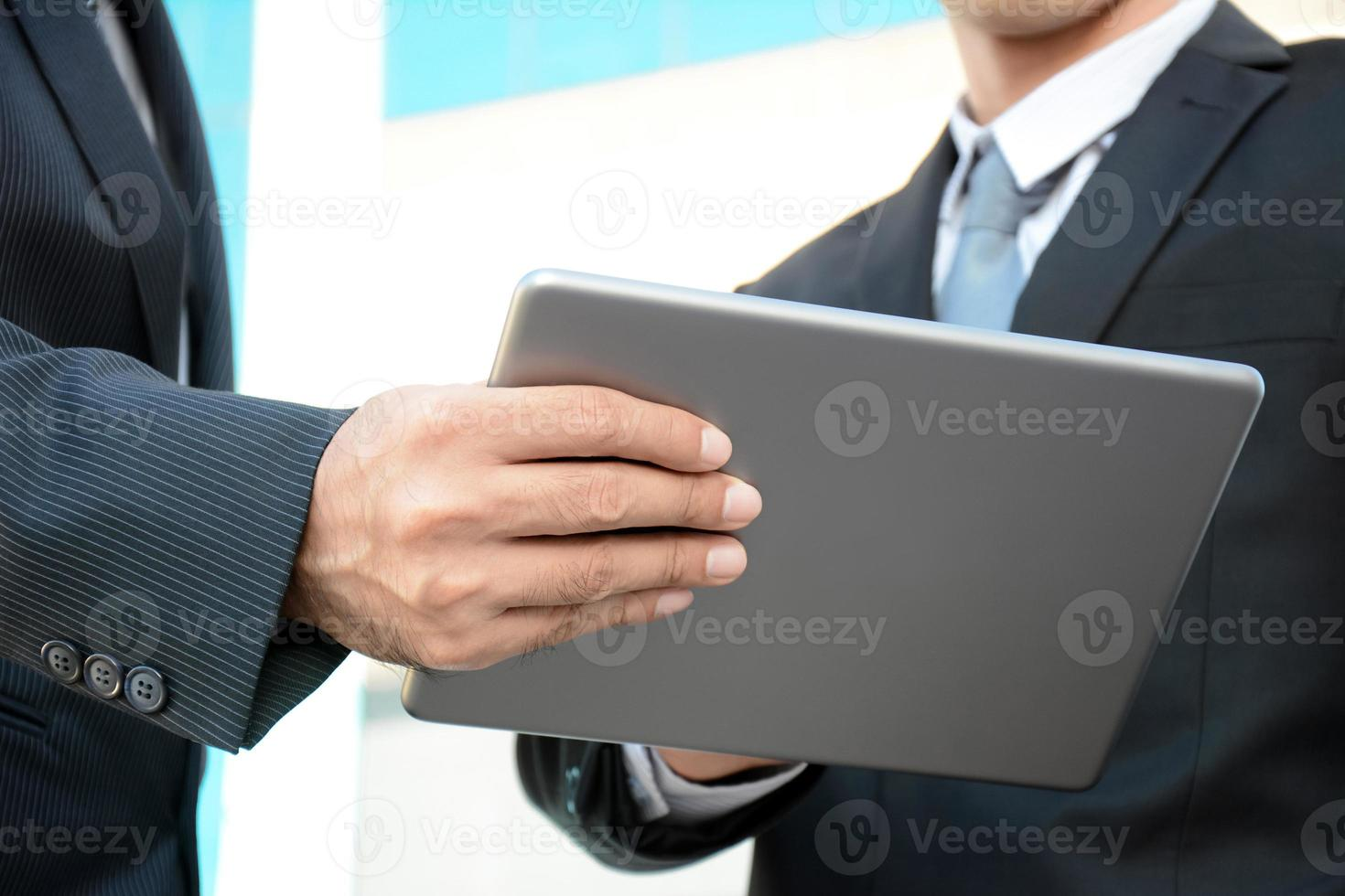 två affärsmän som tittar på surfplattan foto