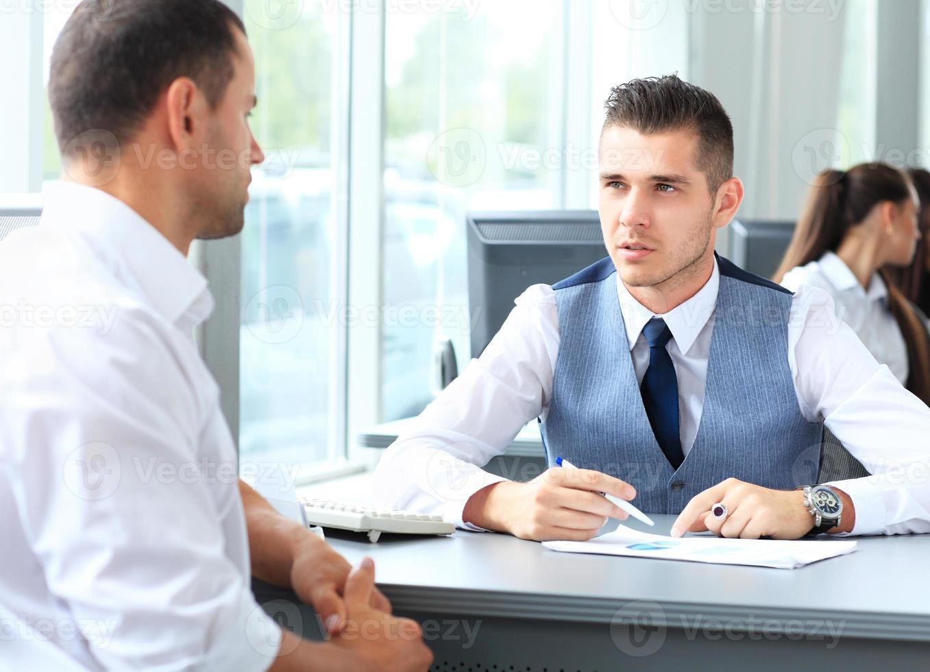 glada affärsmän som pratar på mötet på kontoret foto