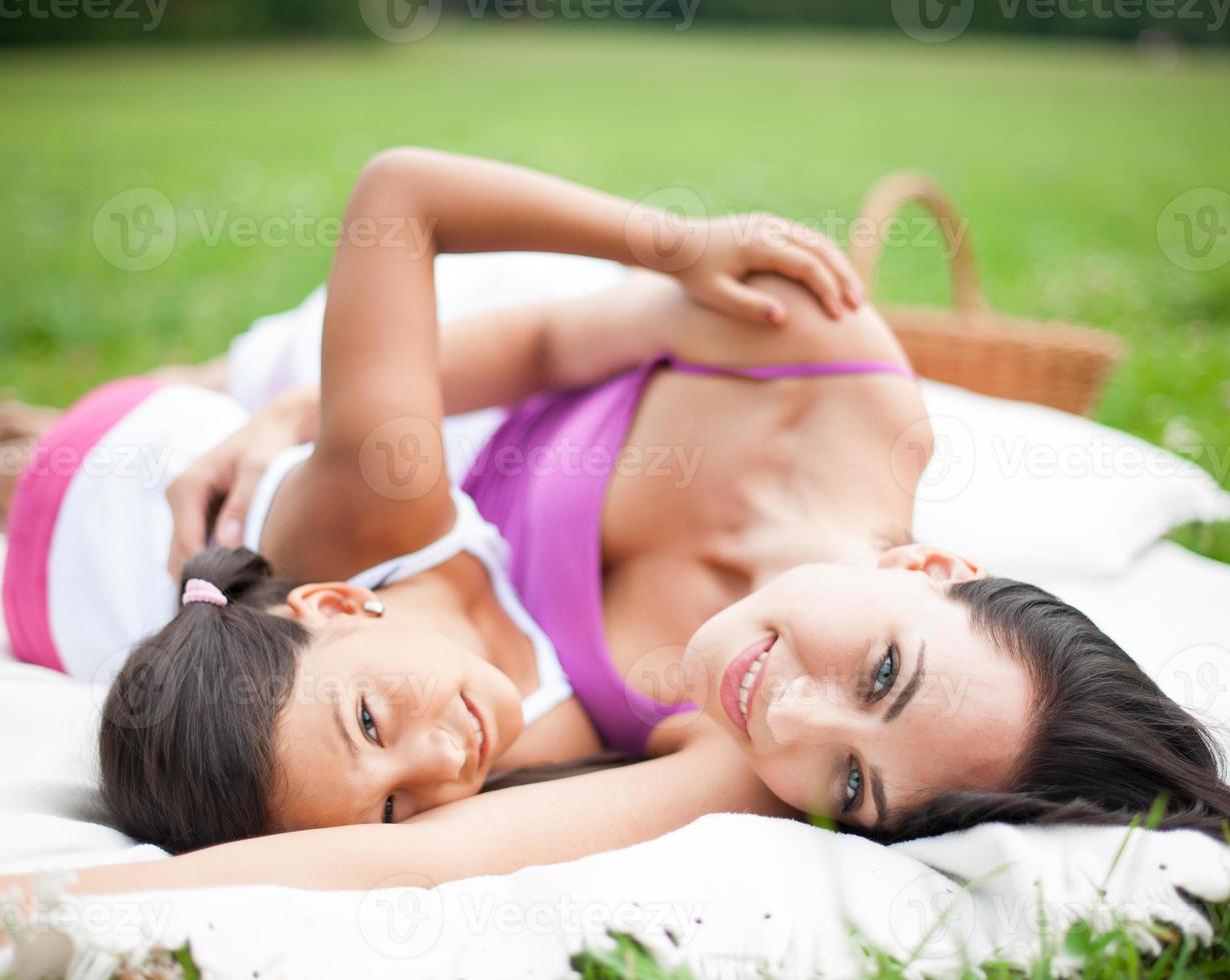 mamma och dotter som ligger på picknickfilt foto
