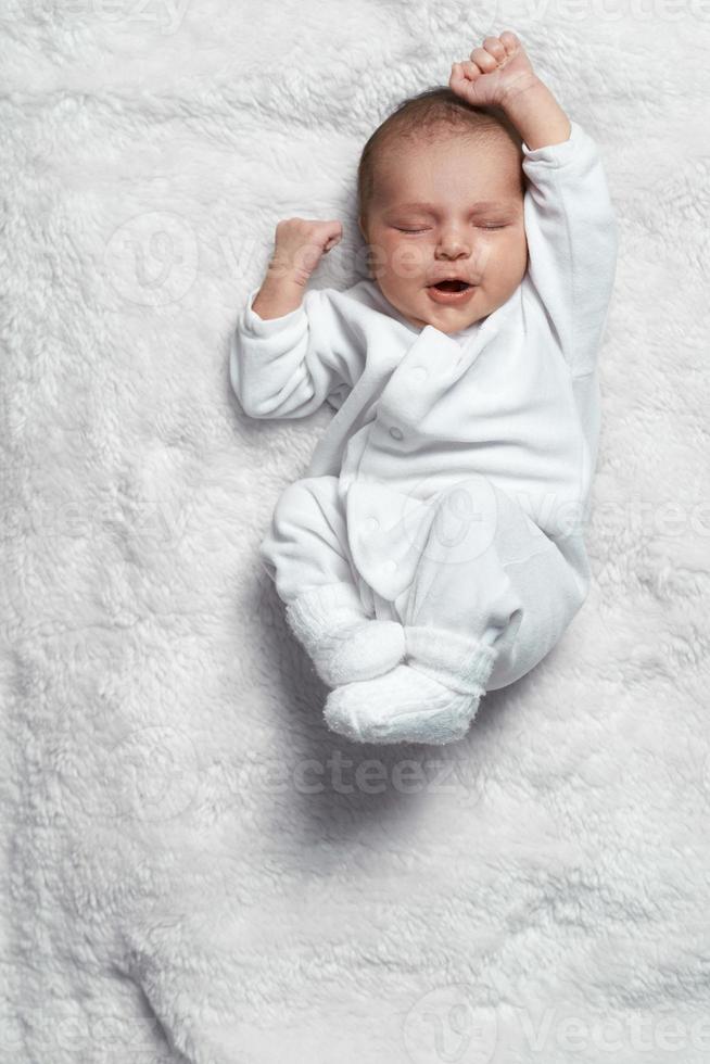 spädbarn gäspar sträcker sig på vit päls foto