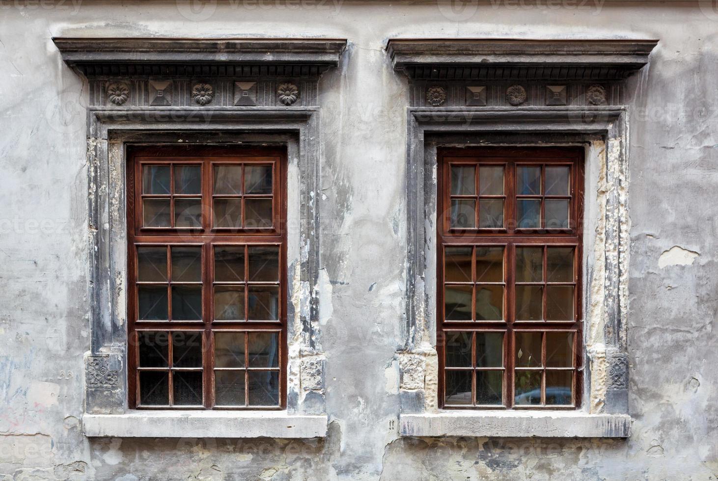 två fönster på en gammal grå stuckaturvägg. foto
