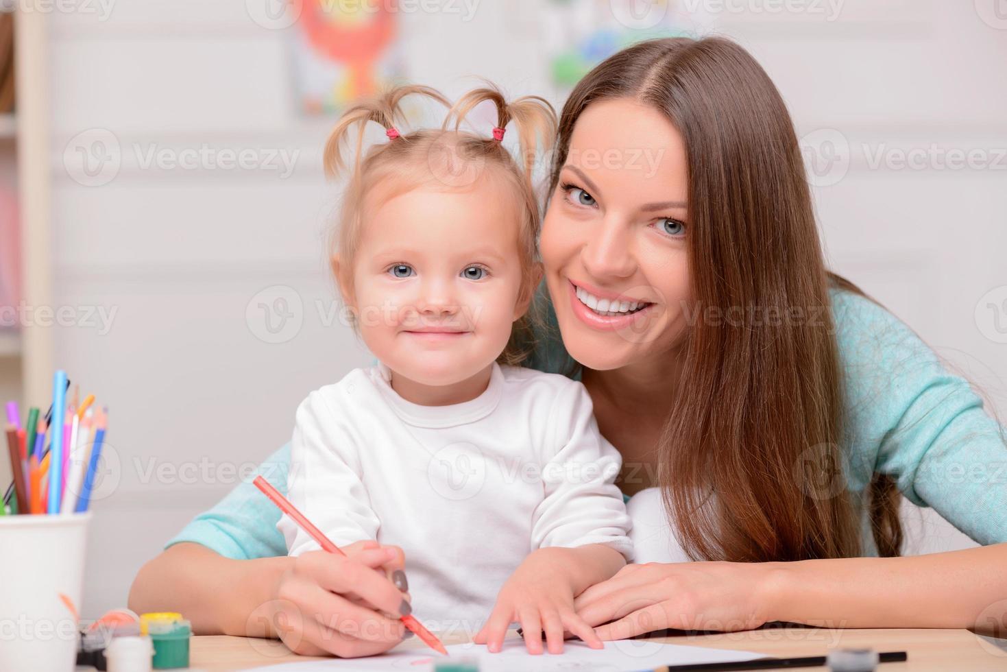 ganska ung kvinna tillbringar tid med sitt barn foto