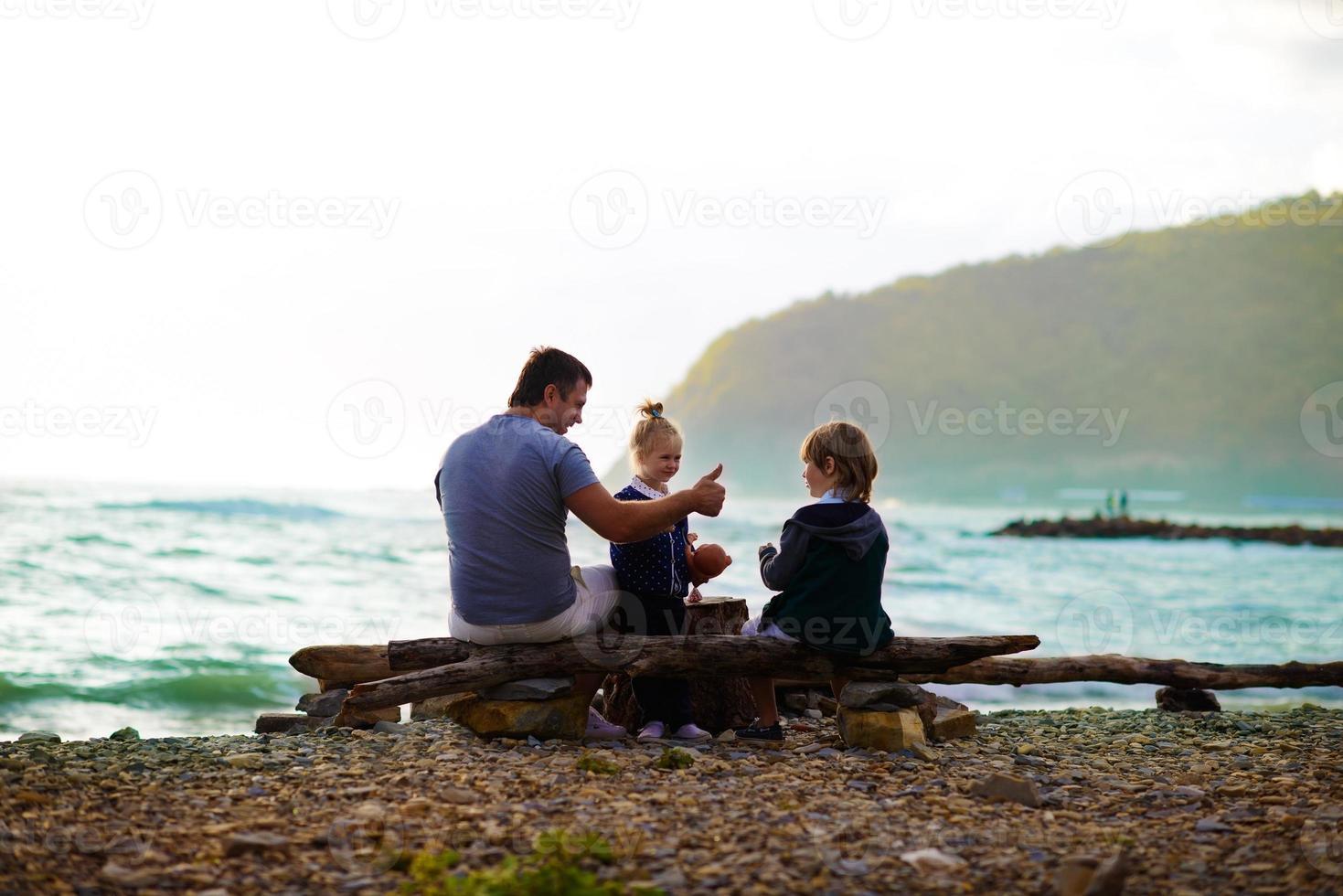 far sitter med sina barn på stranden foto