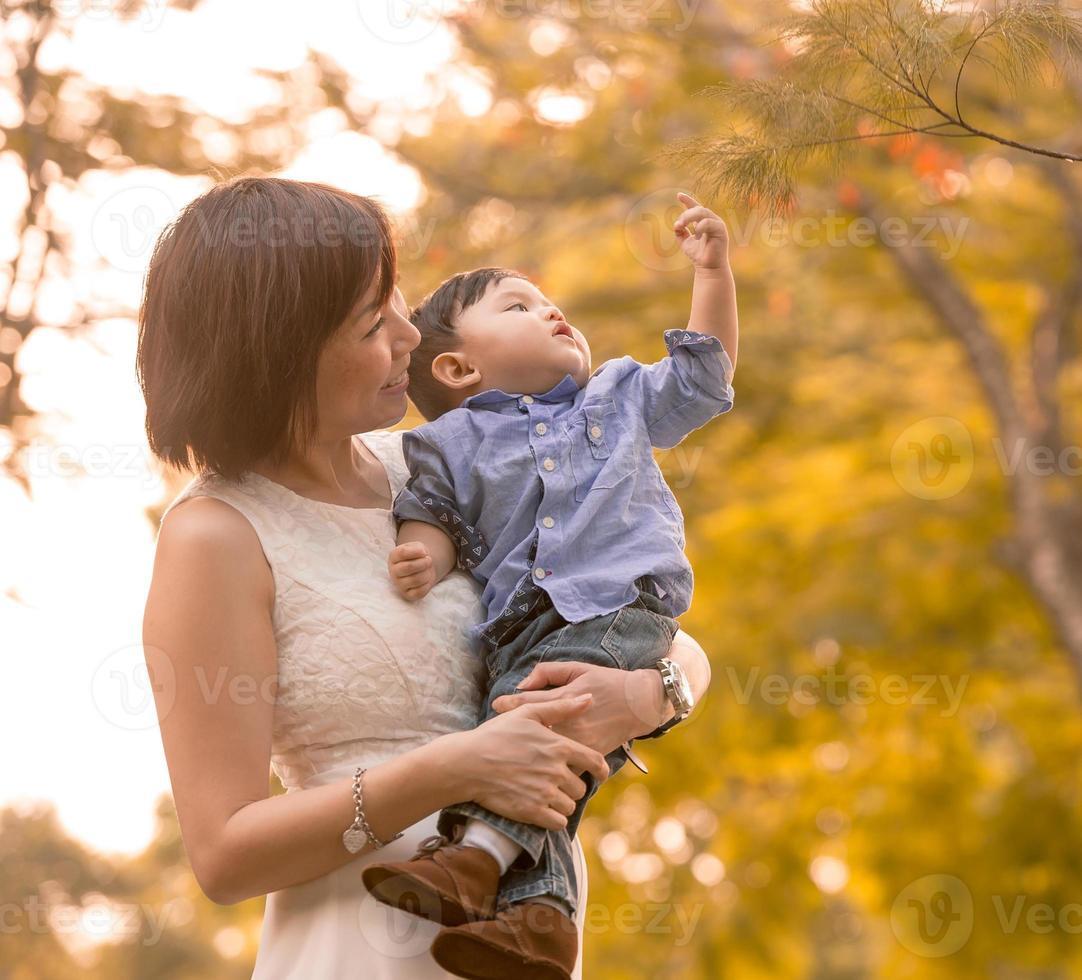 asiatisk mor och son som har kul utomhus foto
