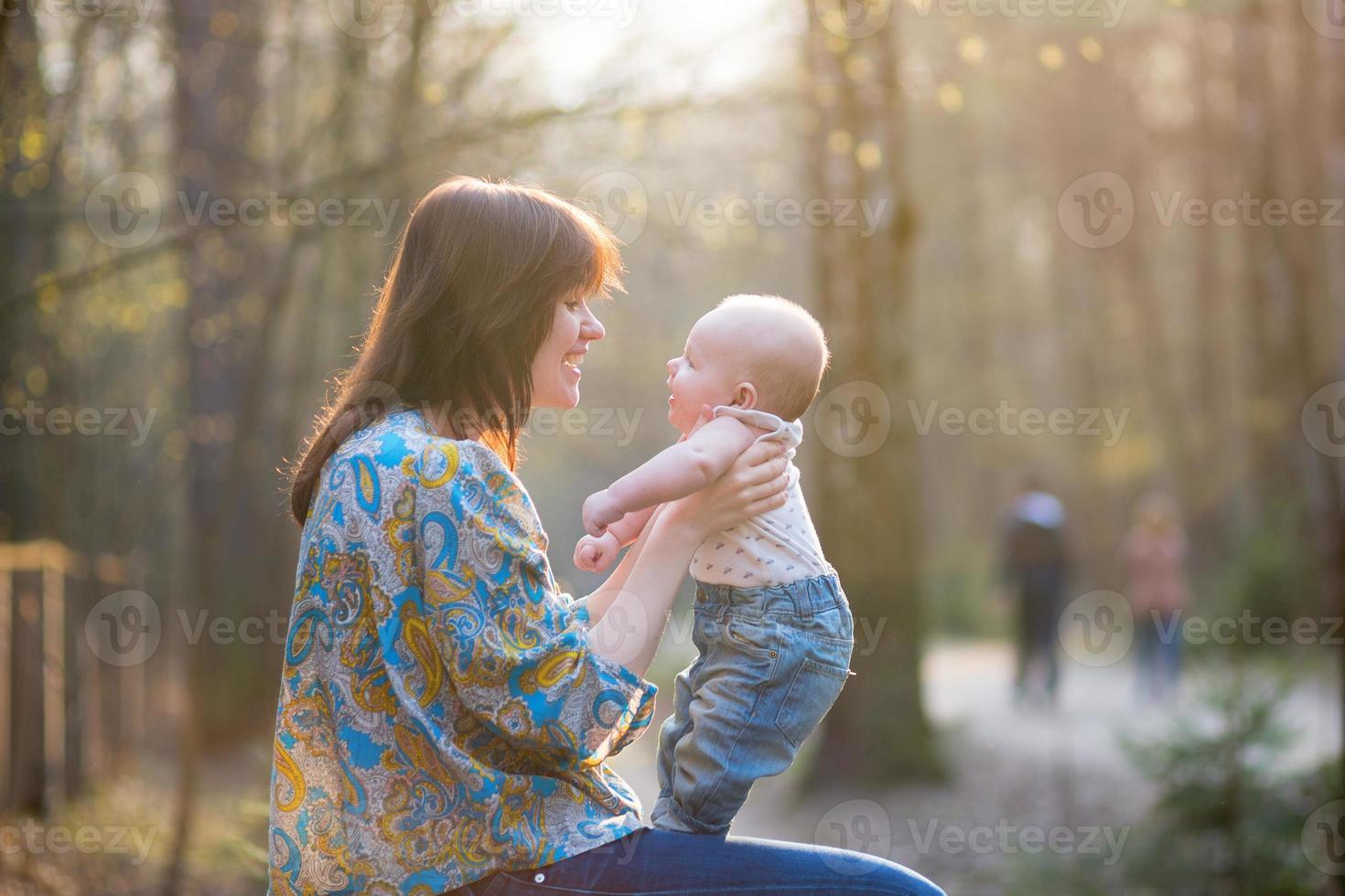 ung mamma med sin lilla baby i skogen foto