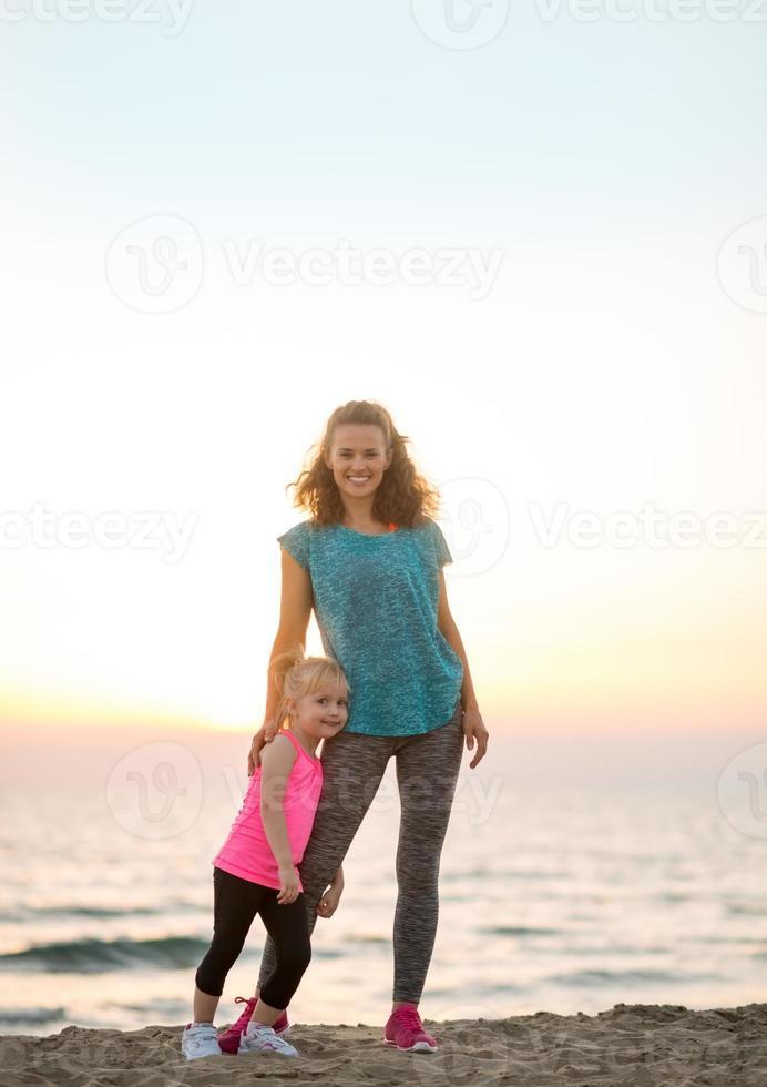 porträtt av frisk mamma och baby flicka på stranden foto
