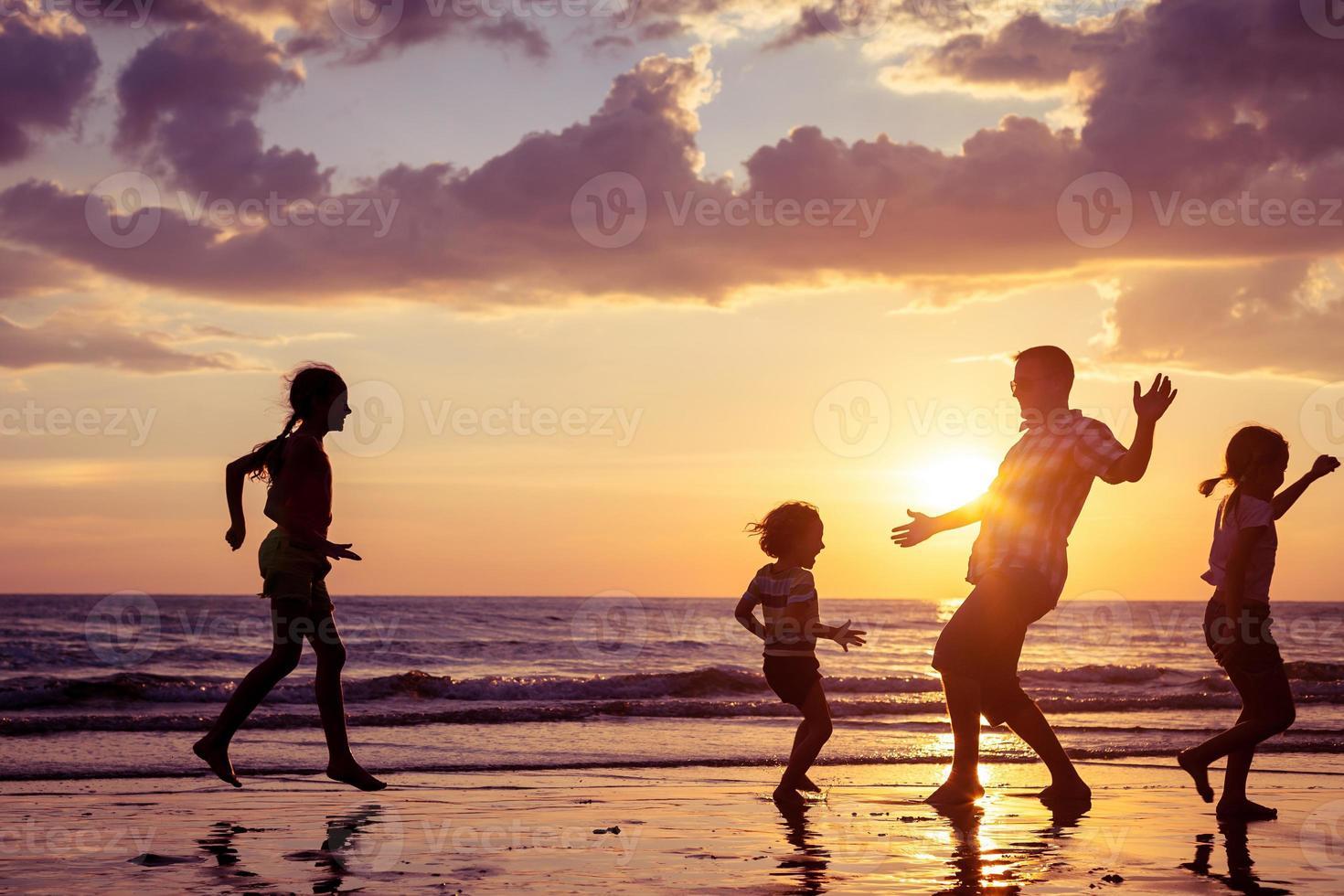 far och barn som leker på stranden foto