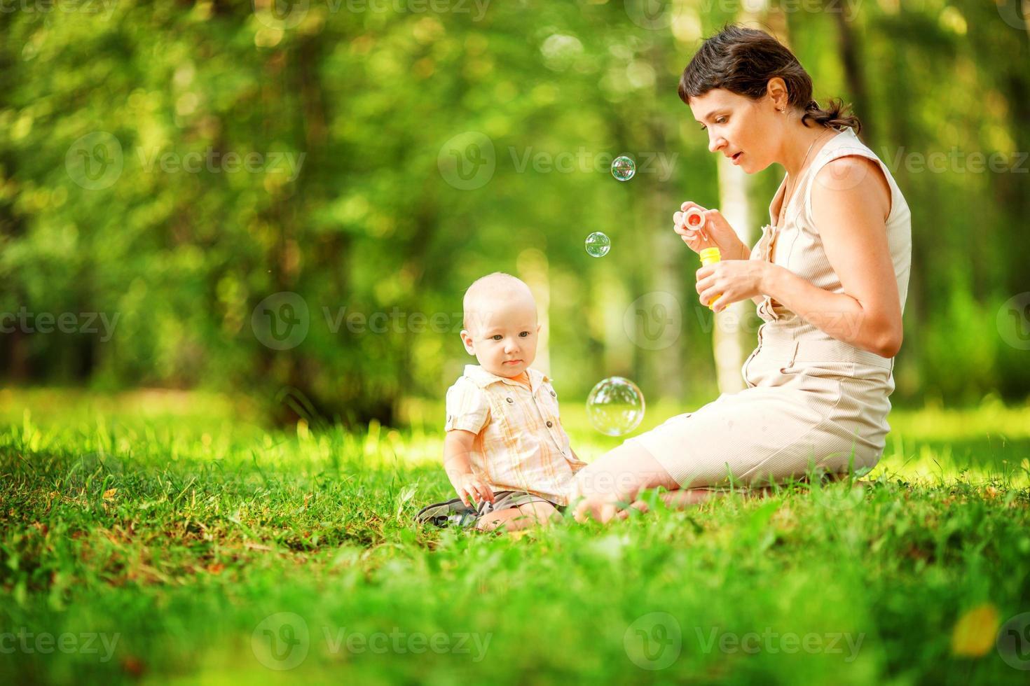 mamma och barn blåser bubblor i parken. foto