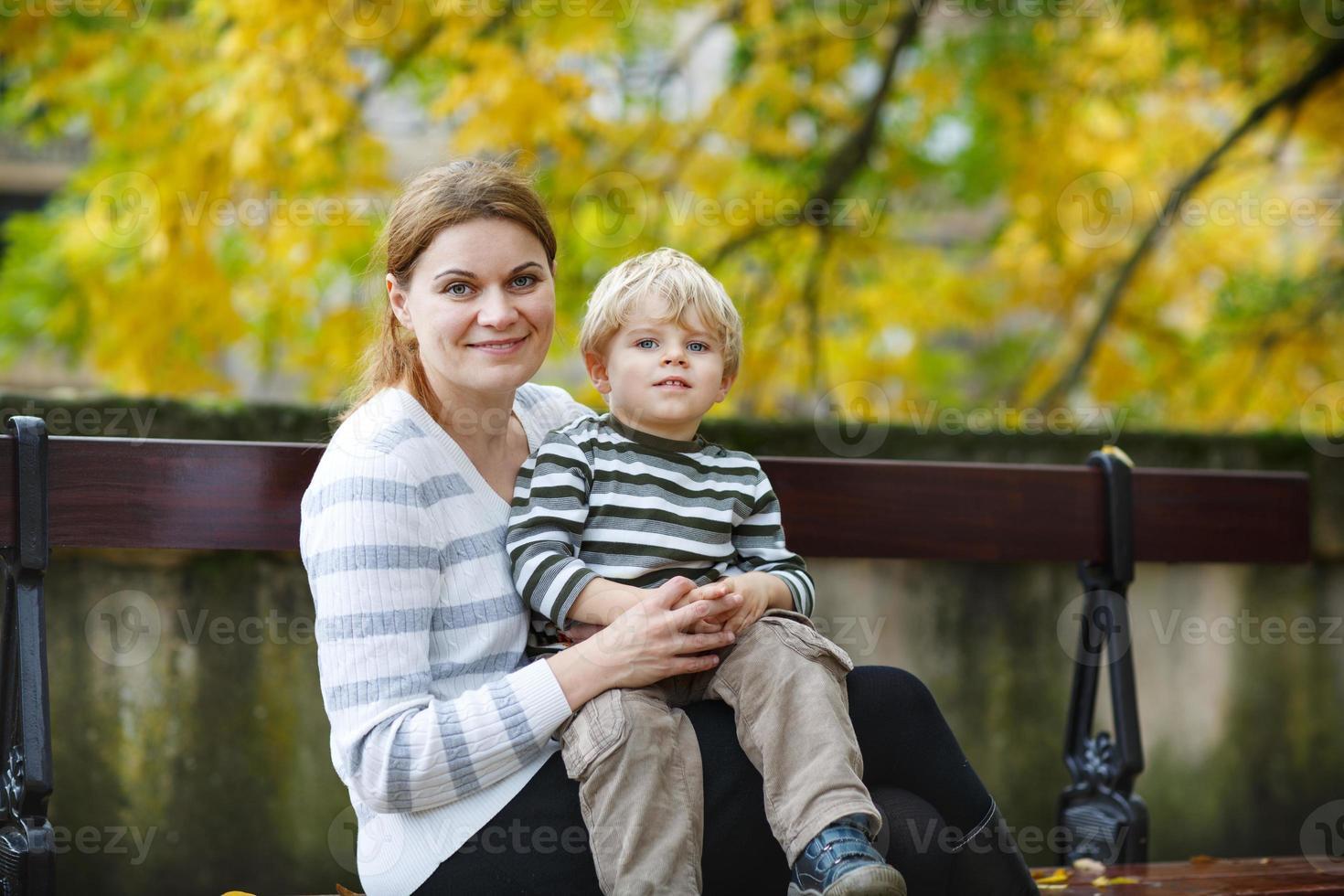 bedårande liten son och mamma i höststad. foto