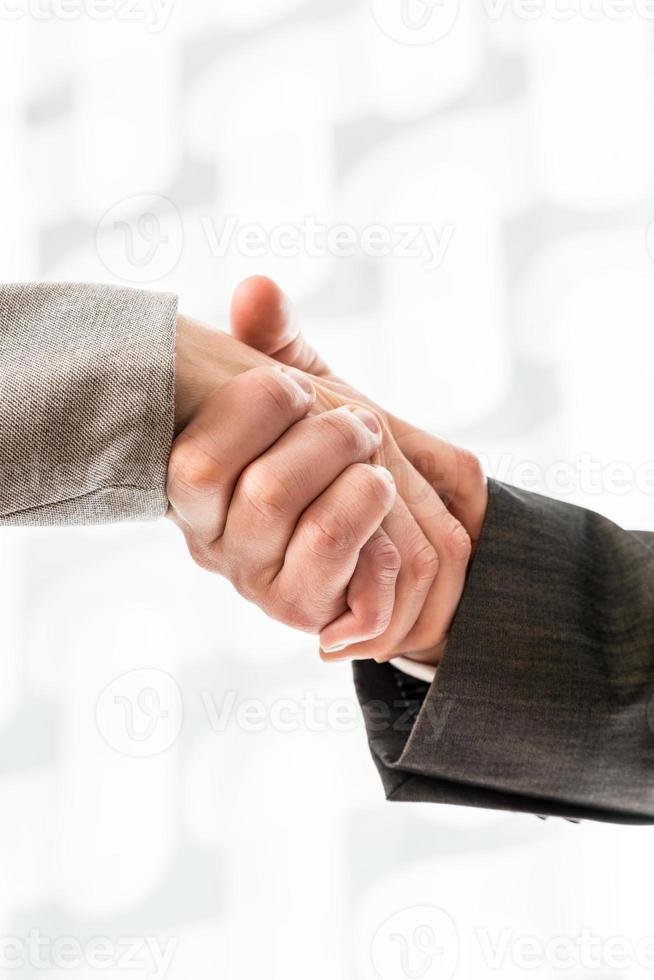 affärsman och affärskvinna i kostymer som skakar hand foto