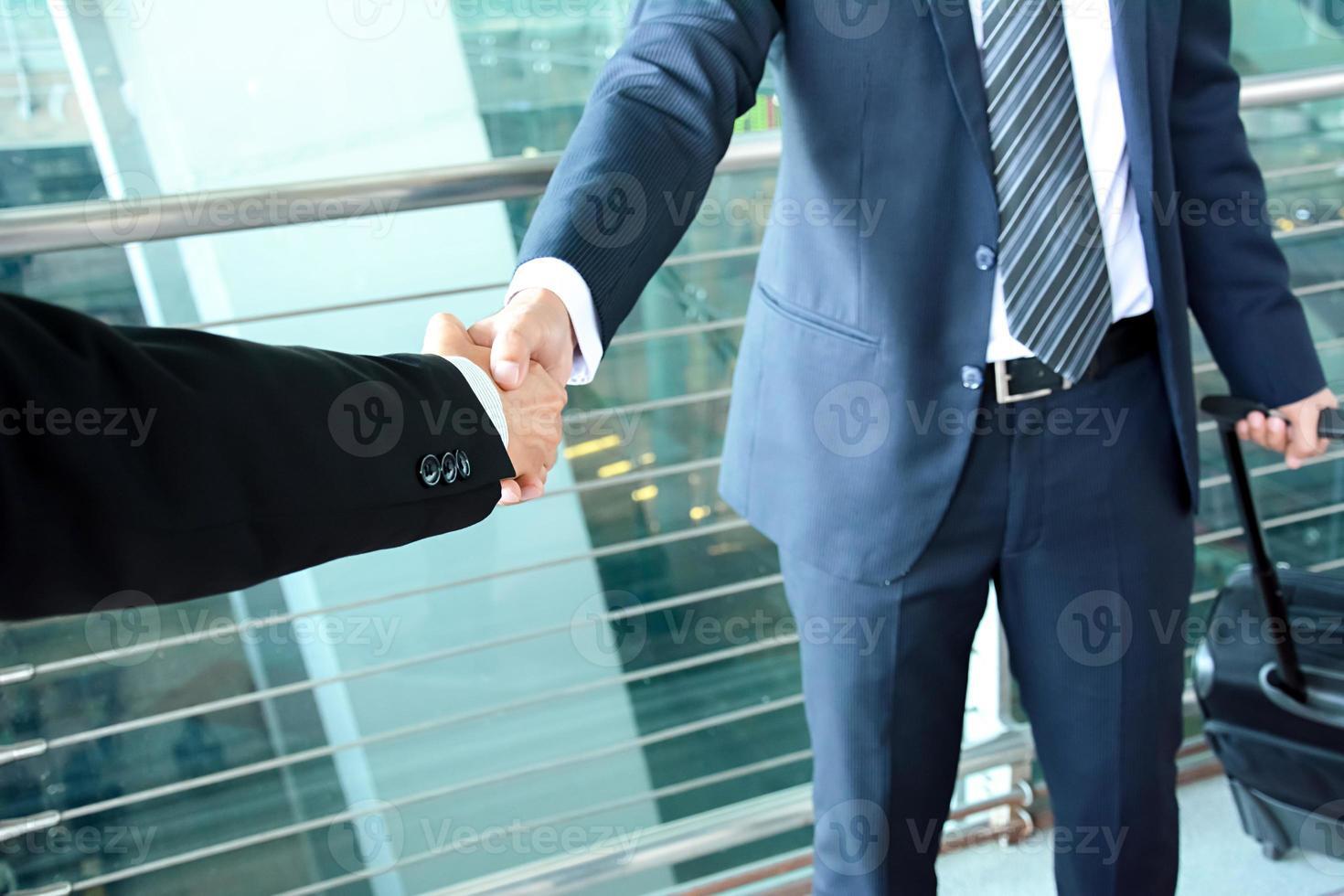 handskakning av affärsmän på flygplatsen - affärsresor koncept foto