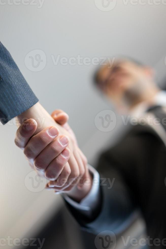 affärsman och kvinna handskakning på kontoret foto