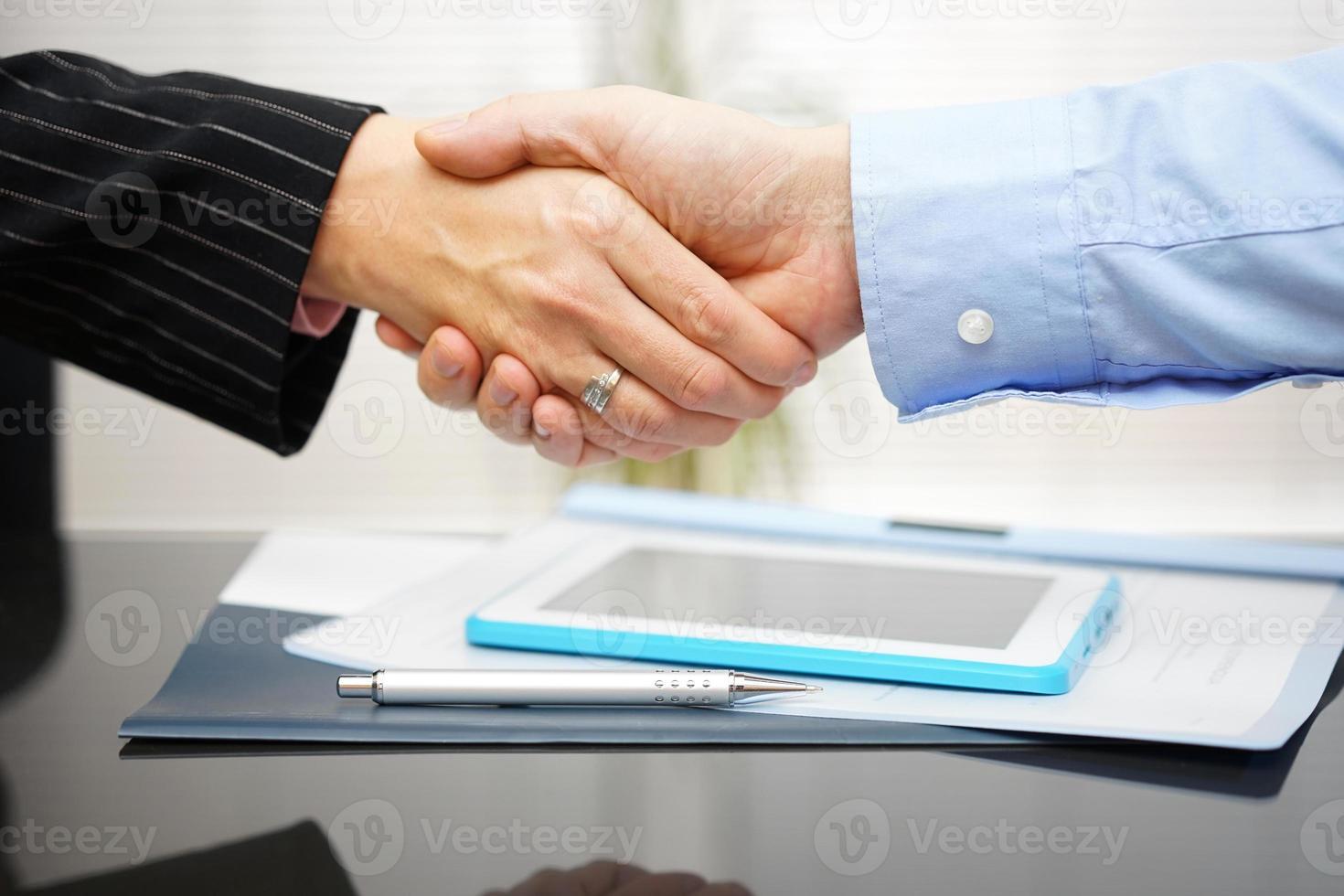 affärsman och affärskvinna handskakar över dokument och presentation foto