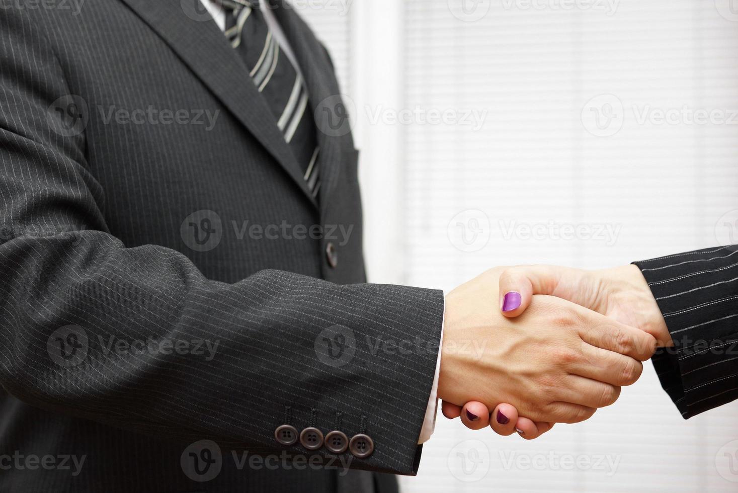 handskakning av affärspartners, man och kvinna på kontoret foto