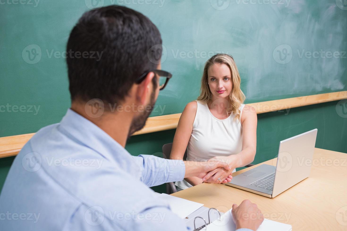 affärskvinna som skakar hand med mannen under intervjun foto