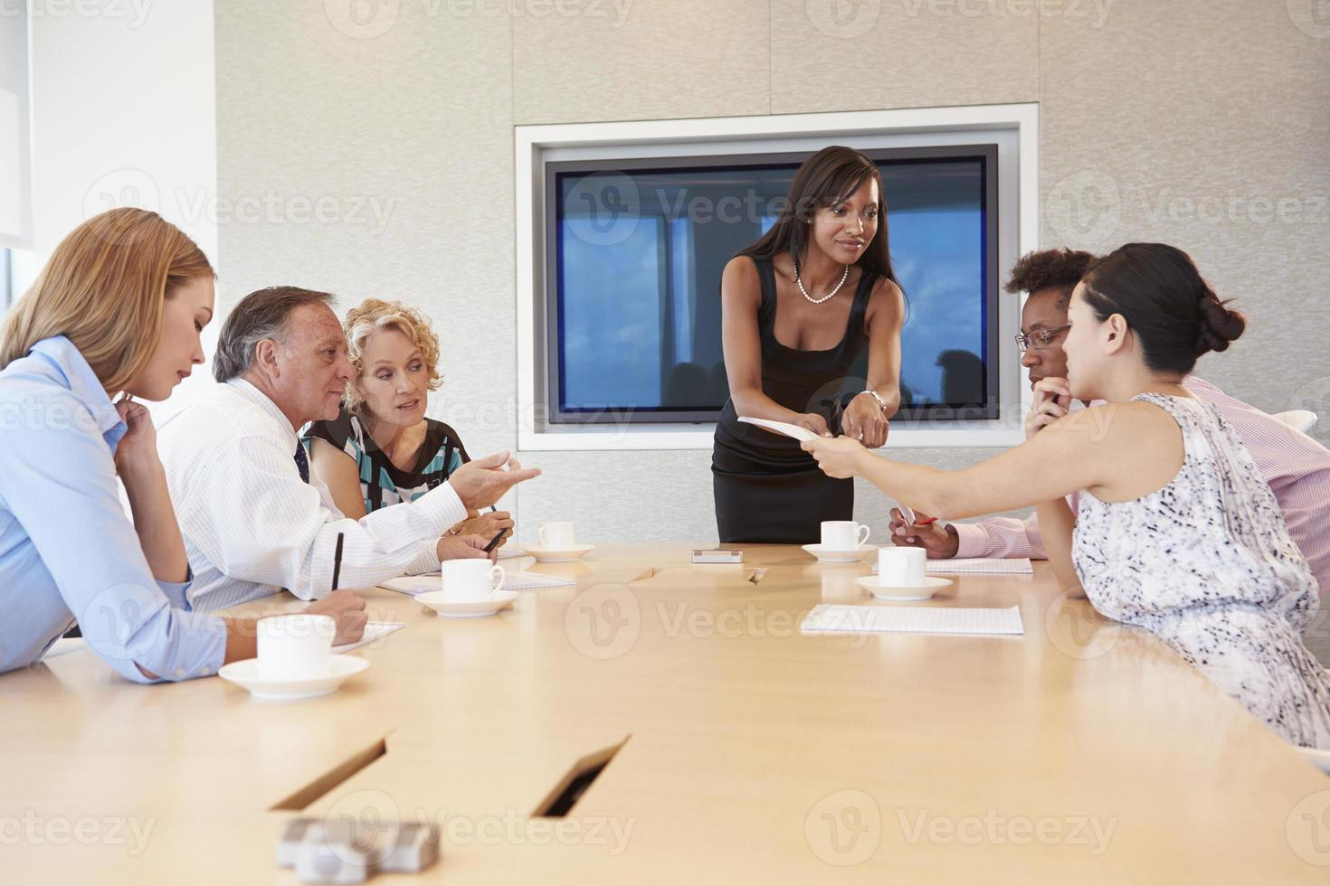 affärskvinna vid skärm adressera styrelsens möte foto