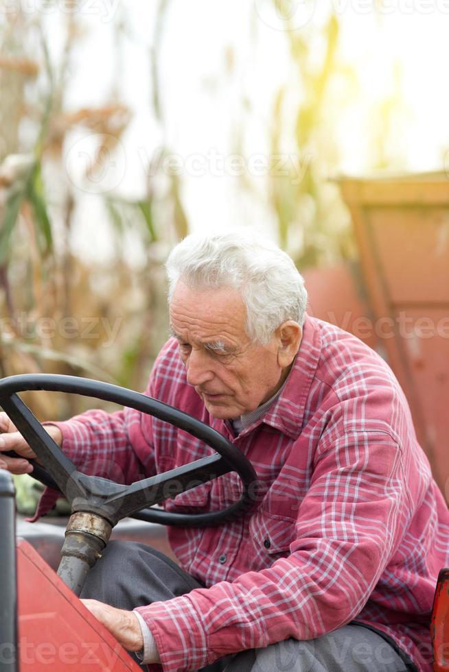 äldre man od traktor foto