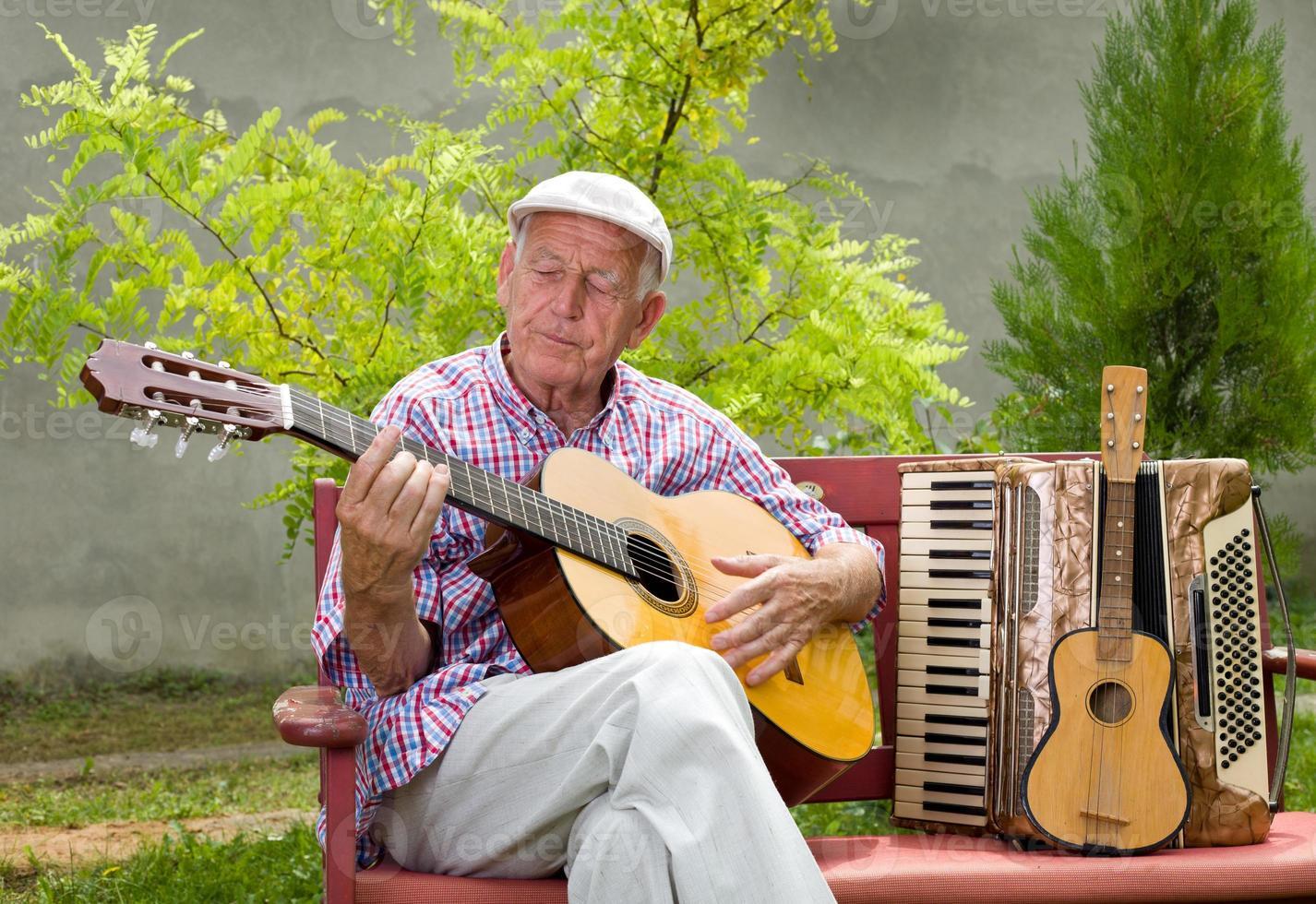 äldre man med gitarr foto