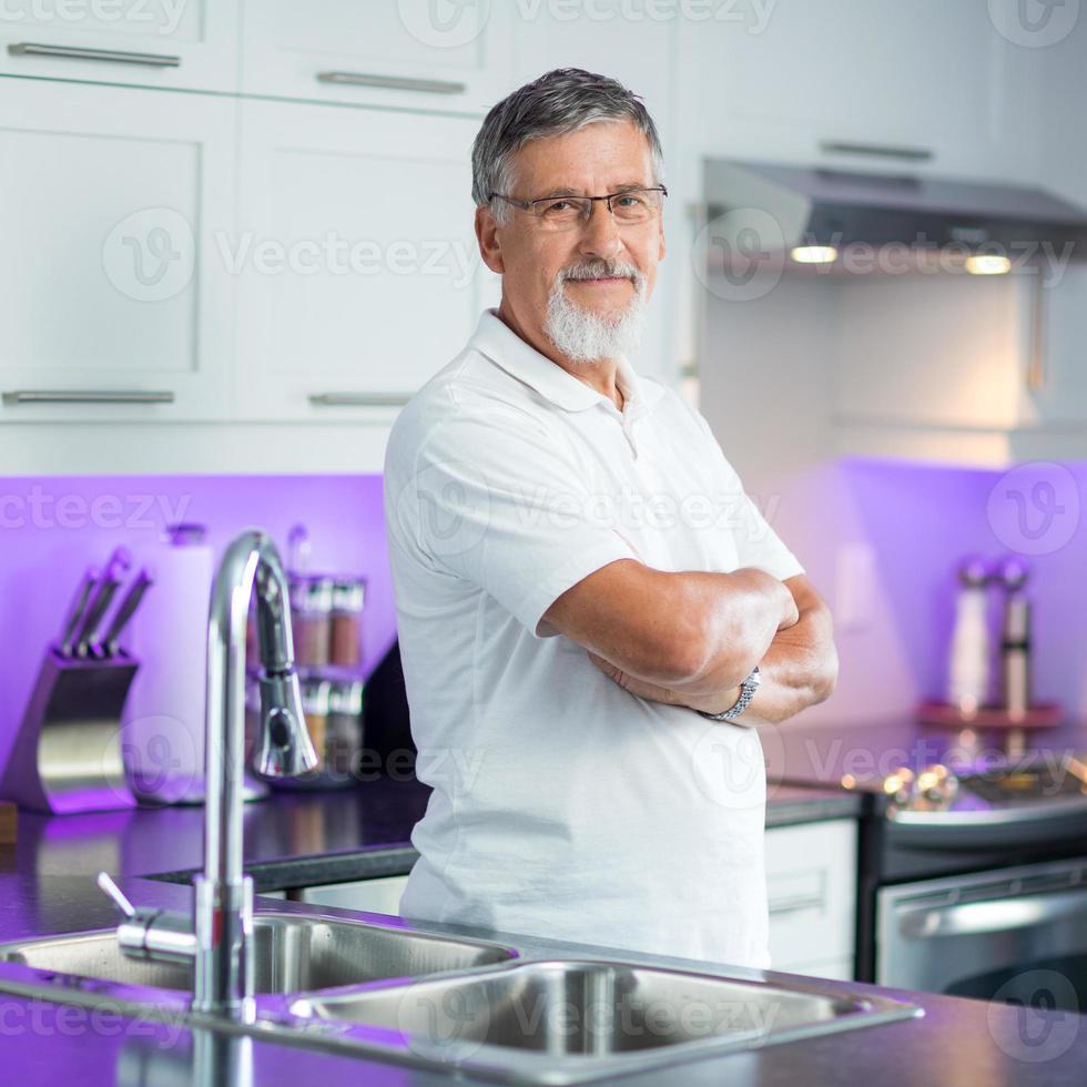 äldre man som står i sitt renoverade, moderna kök, foto