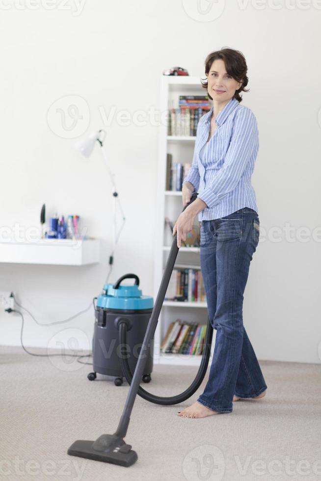 leende kvinna dammsugar vardagsrummet foto