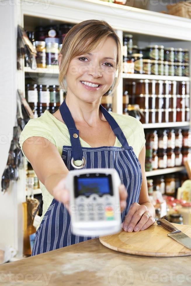 försäljningsassistent som överlåter kreditkortsmaskin till kunden foto
