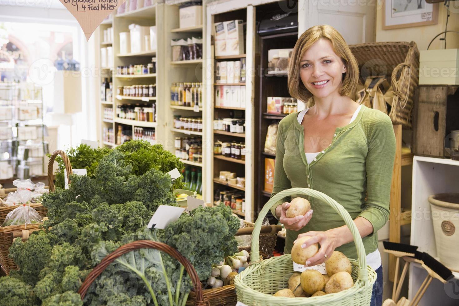 kvinna i marknaden tittar på potatis foto
