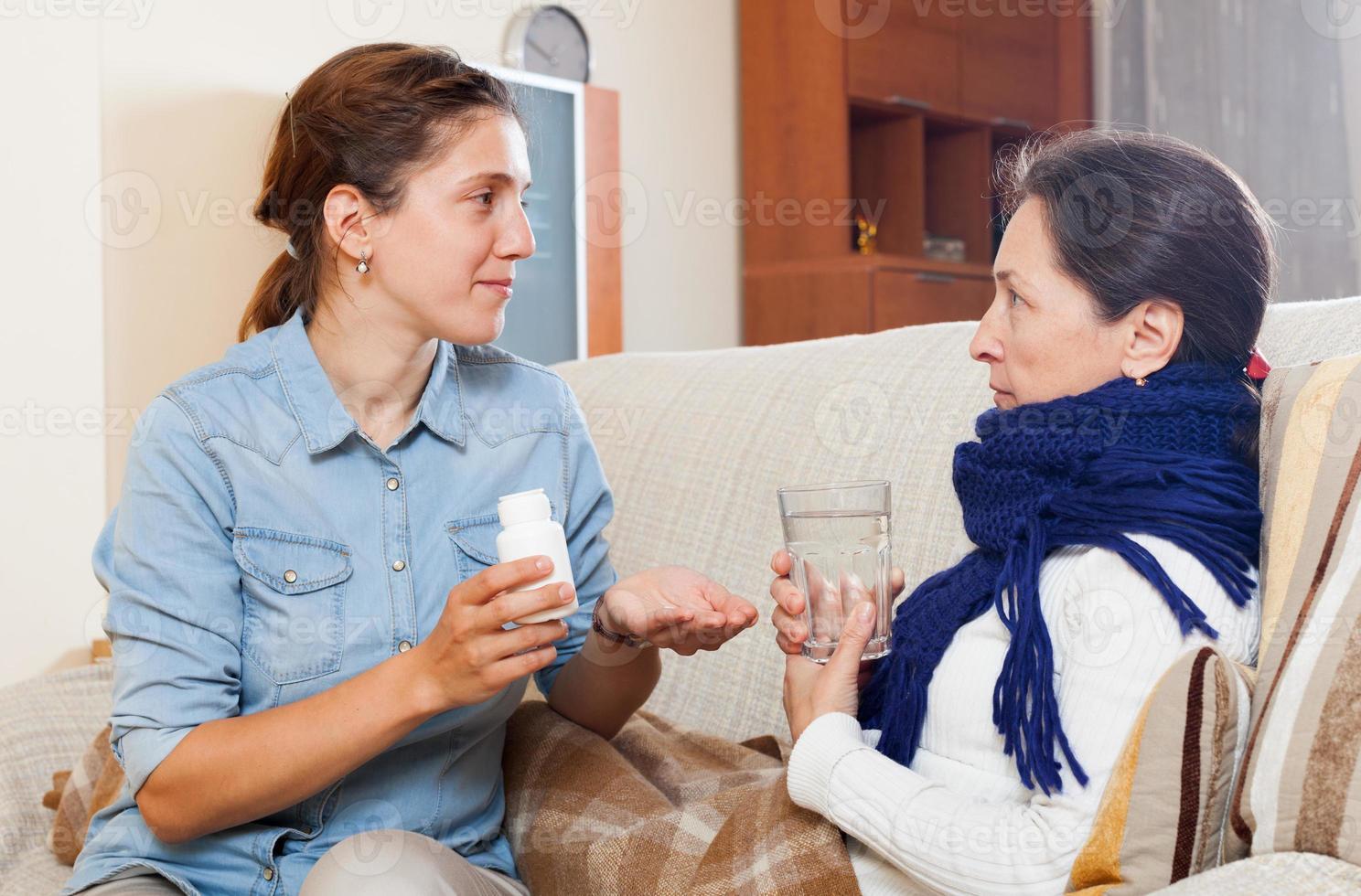kvinna som tar hand om sjuk mogen mamma foto
