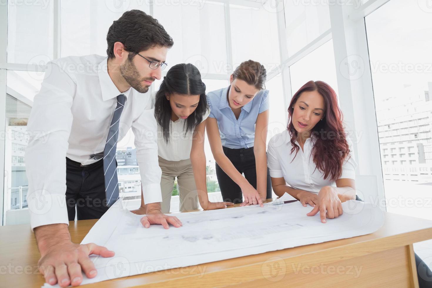 affärsgrupp som läser arbetsplaner foto