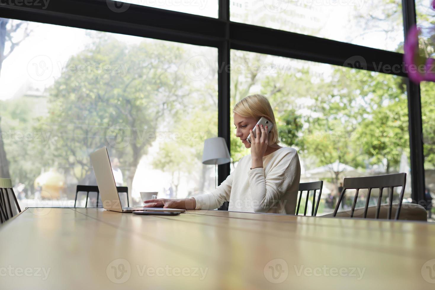 frilanser som arbetar på distansprat på smarttelefon i café foto
