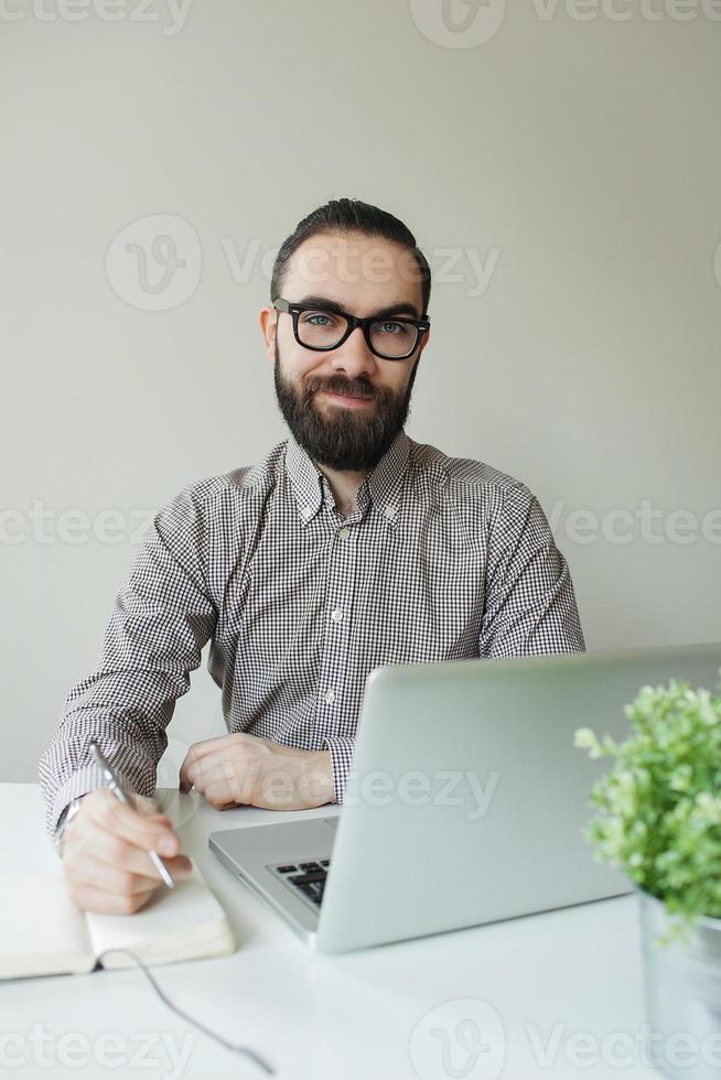 man med skägg i glasögon med anteckningar med laptop anteckningsblock foto