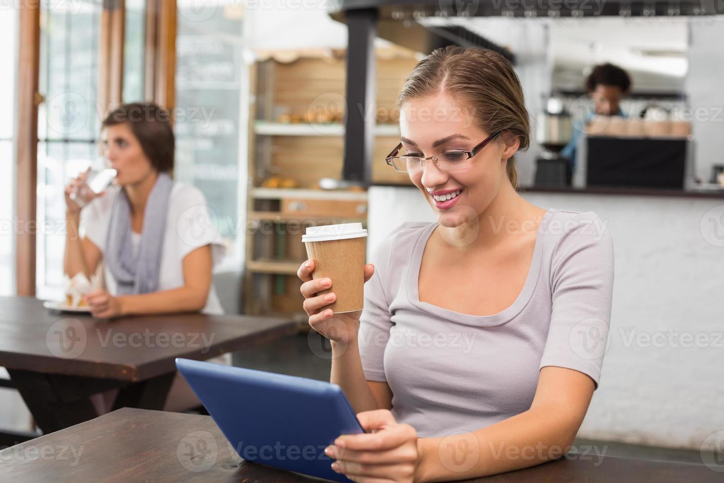 vacker blondin njuter av ett kaffe med hjälp av TabletPC foto