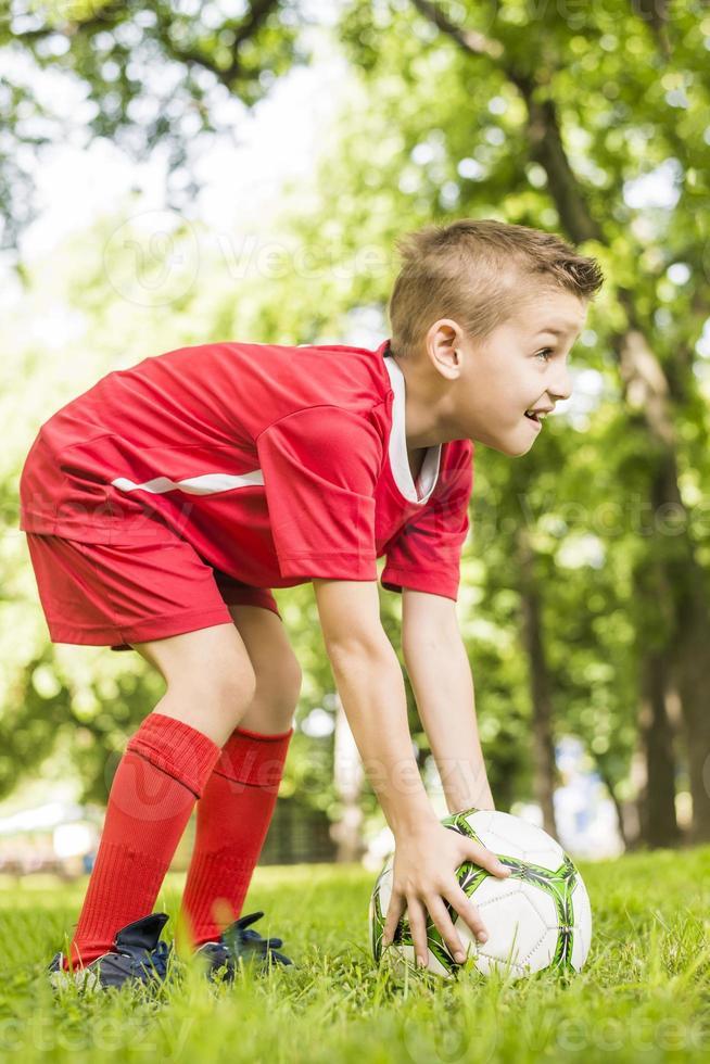 ung pojke som håller fotboll foto