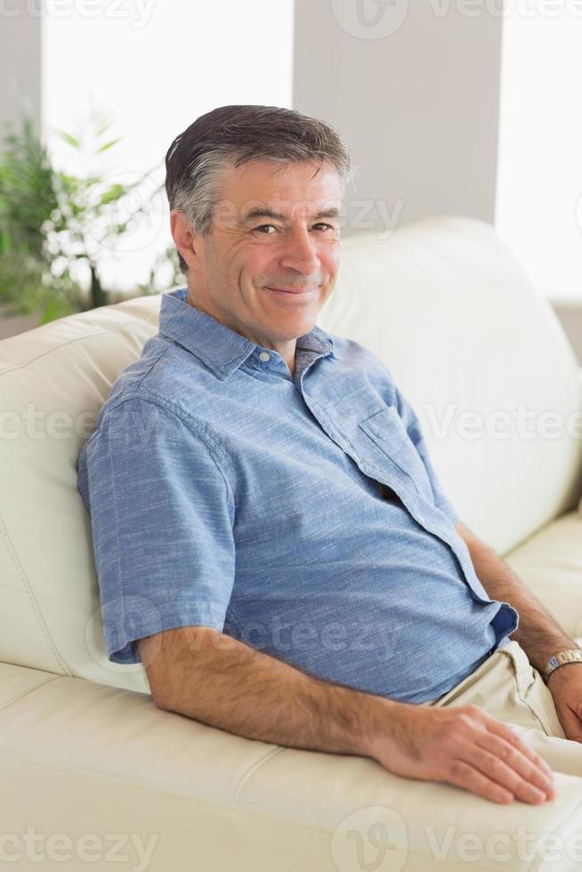 leende man sitter på en soffa foto