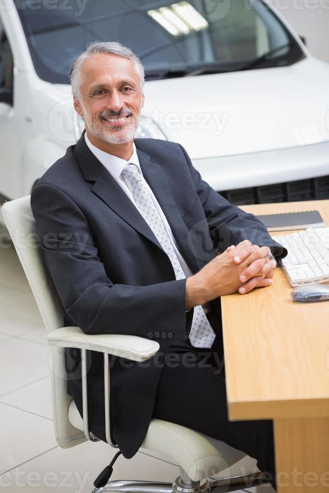 glad affärsman som arbetar vid sitt skrivbord foto
