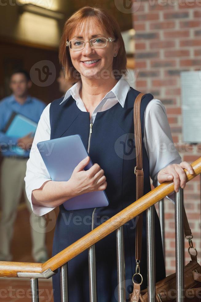 kvinnlig mogen student som håller hennes surfplatta poserar på trappan foto