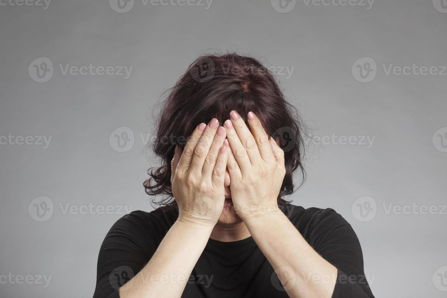 mogen kvinna som täcker ögonen foto