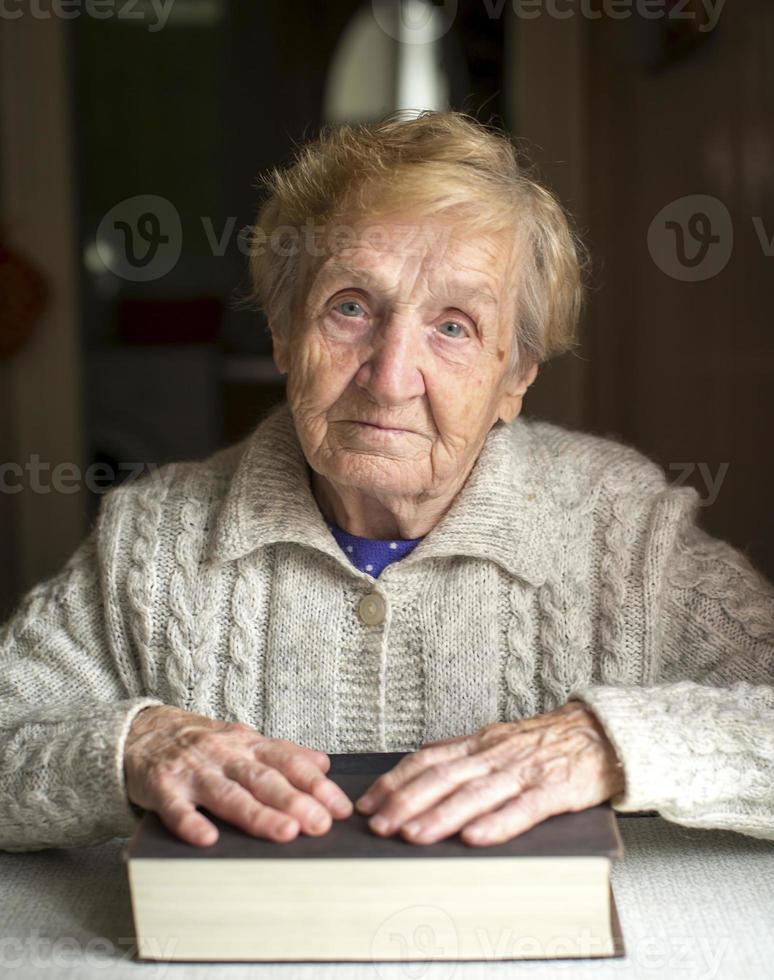 gammal kvinna som sitter vid ett bord med en bok. foto