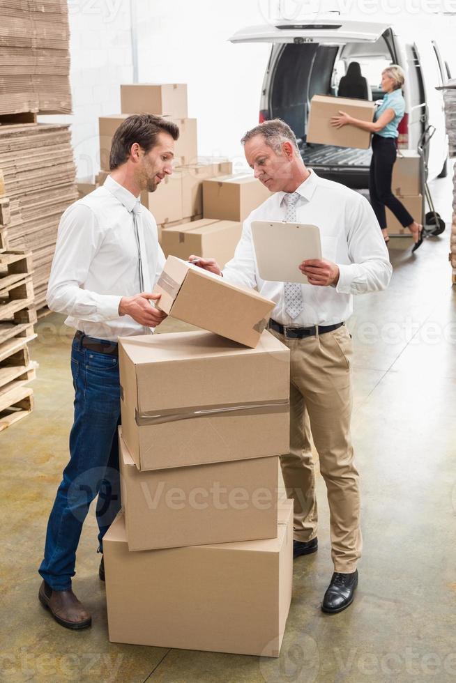 lagerchefer som kontrollerar deras lista foto