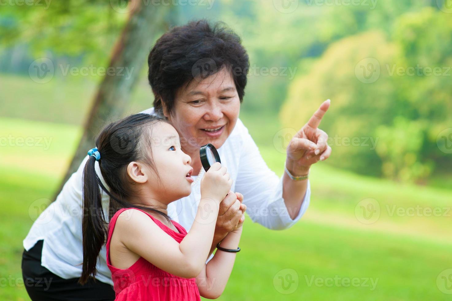 mormor och barnbarn pekar på något i parken foto