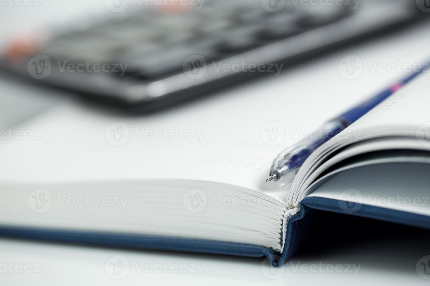 penna, miniräknare på anteckningsboken foto