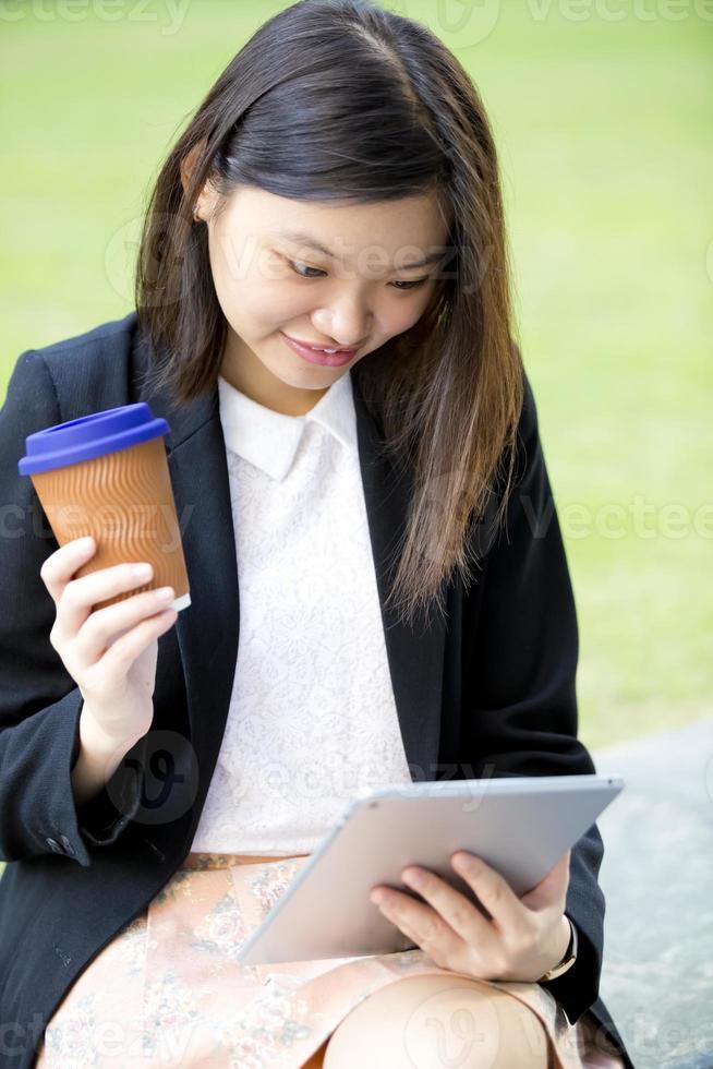 unga kvinnliga asiatiska företagsledare med surfplatta foto
