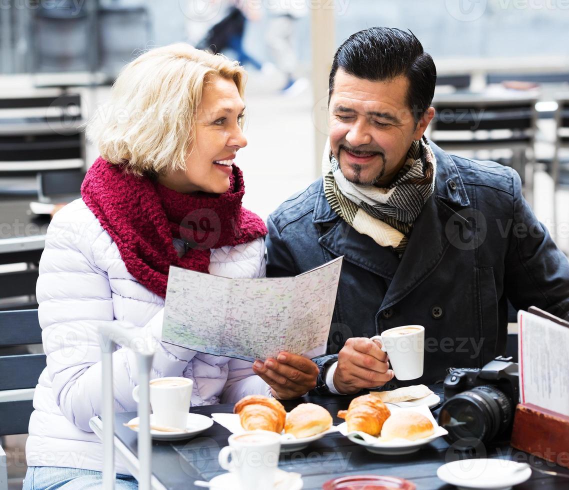 äldre turister läser karta på caféet foto