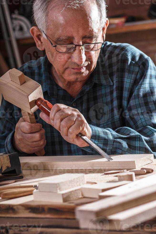 äldre snickare som arbetar med verktyg. foto