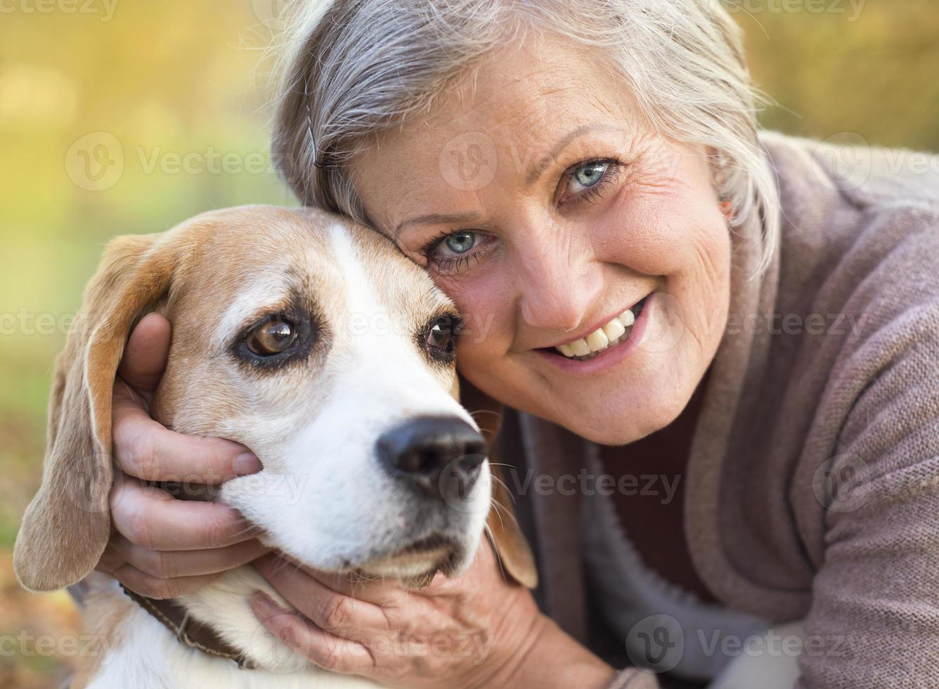 aktiv äldre kvinna kramar hund foto