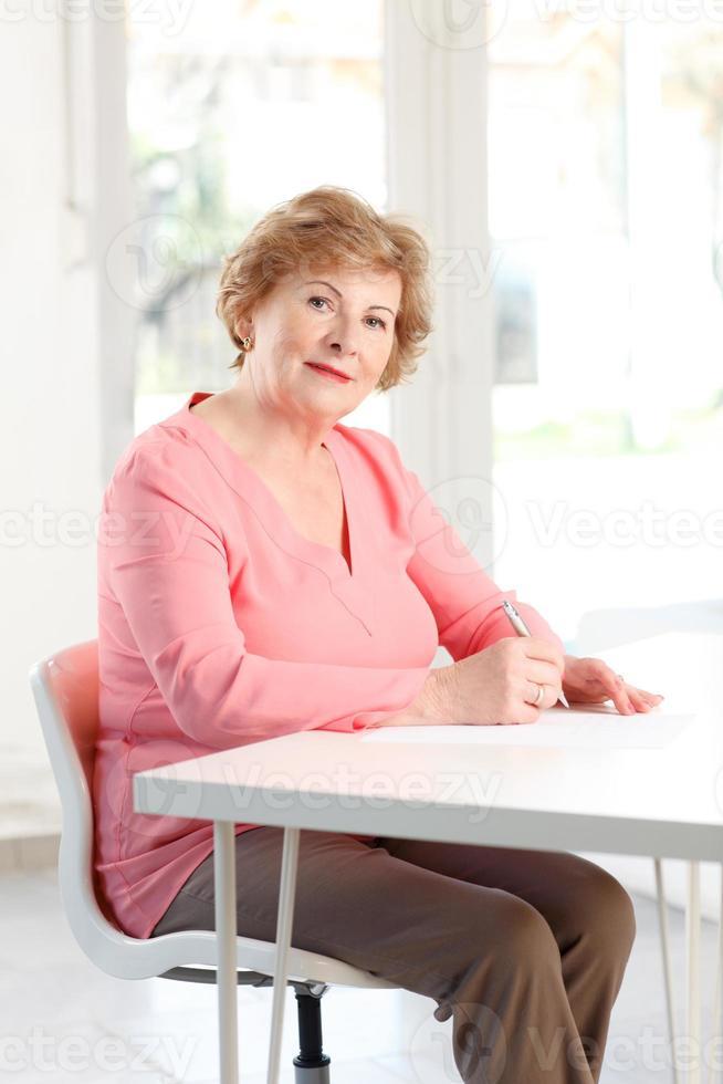 närbild av en äldre kvinna som sitter vid skrivbordet foto