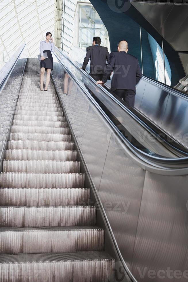 affärsmän på rulltrappa affärskvinna som använder mobiltelefon foto