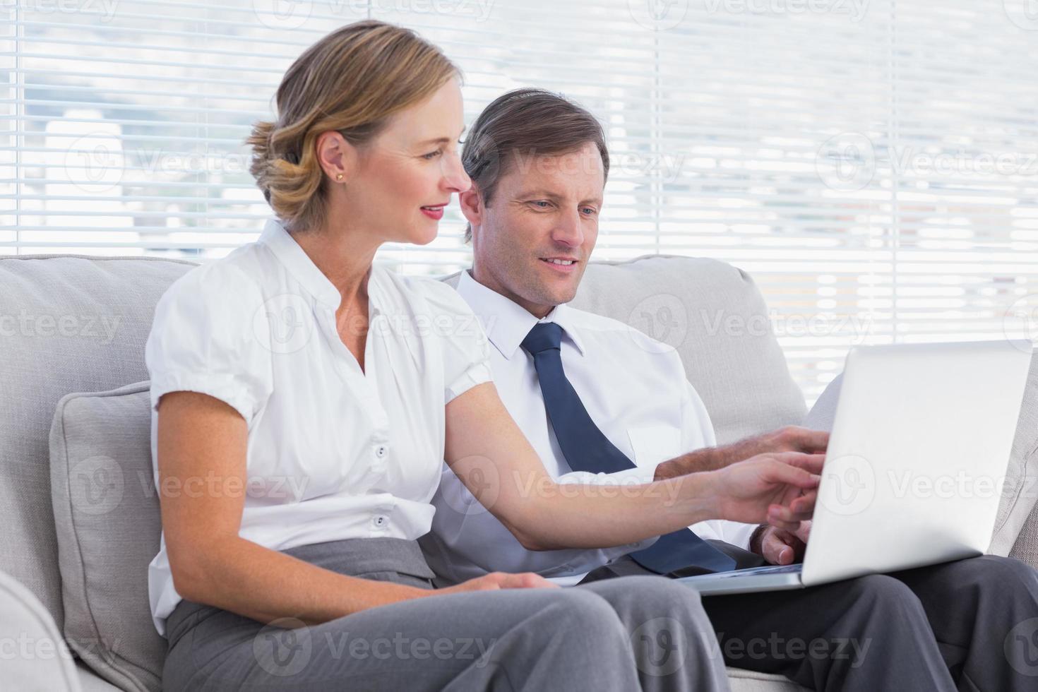 affärsmän tittar på något på laptop foto