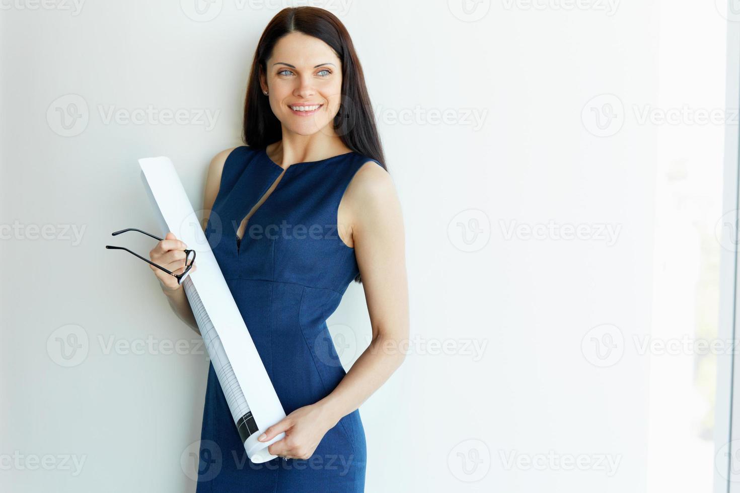 ung kvinnlig arkitekt står på ett kontor. affärsmän foto