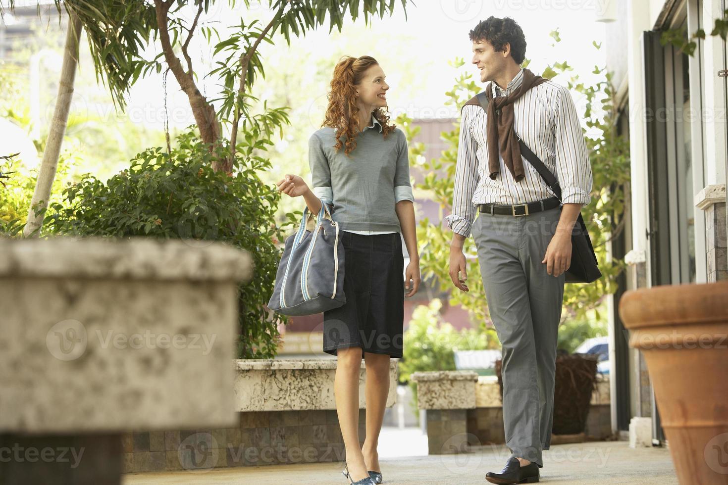 glada affärsmän som går på trottoaren foto